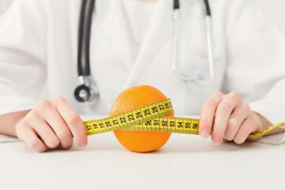 Nutritionist doctor with fruit and measuring tape, closeup. Healthy eating, right nutrition and slimming concept